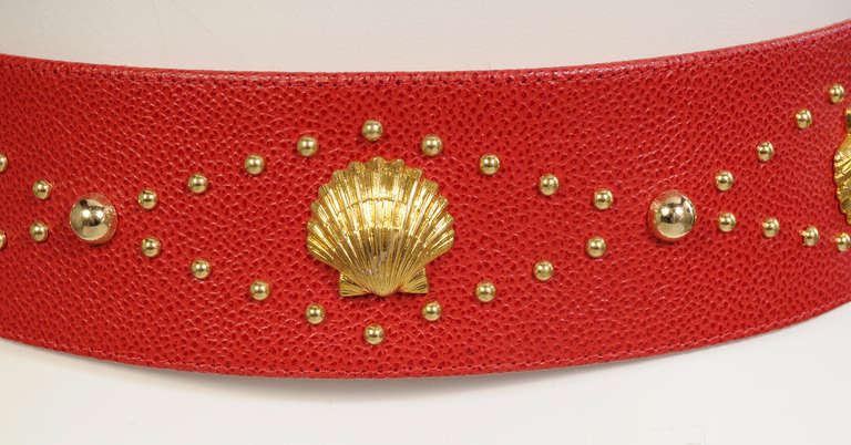Bright red leather is embellished with gold toned beads and sea shells as well as the YSL logo. The belt is marked Yves Saint Laurent, Made in France and size 30/75 on the inside. It is in excellent condition and appears unworn.