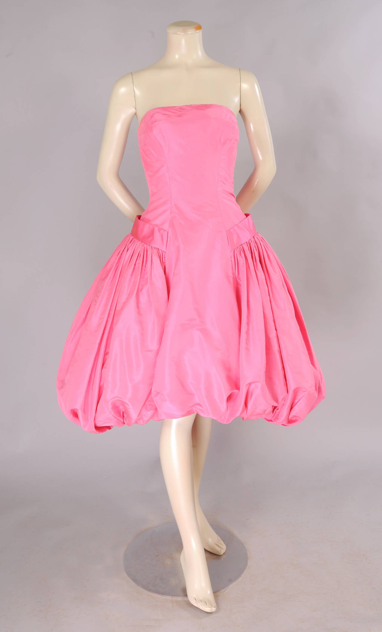 A gorgeous shade of bright pink silk is used to create this glamorous  short evening dress from the 1950's. The dress has a fitted boned bodice, a wide panel at the center front, A horizontal band over each hip terminates in a bow at the center