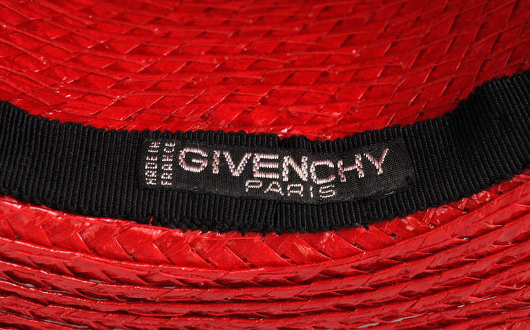 Bright and shiny red straw is combined with a wide red grosgrain ribbon  to create this feminine version of the classic straw boater from Givenchy Haute Couture. It bears the couture label and it is in excellent condition.