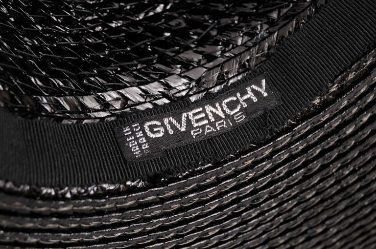 A tall and narrow crown gives this black straw hat from Givenchy Haute Couture a very stylish look. It is in excellent condition.