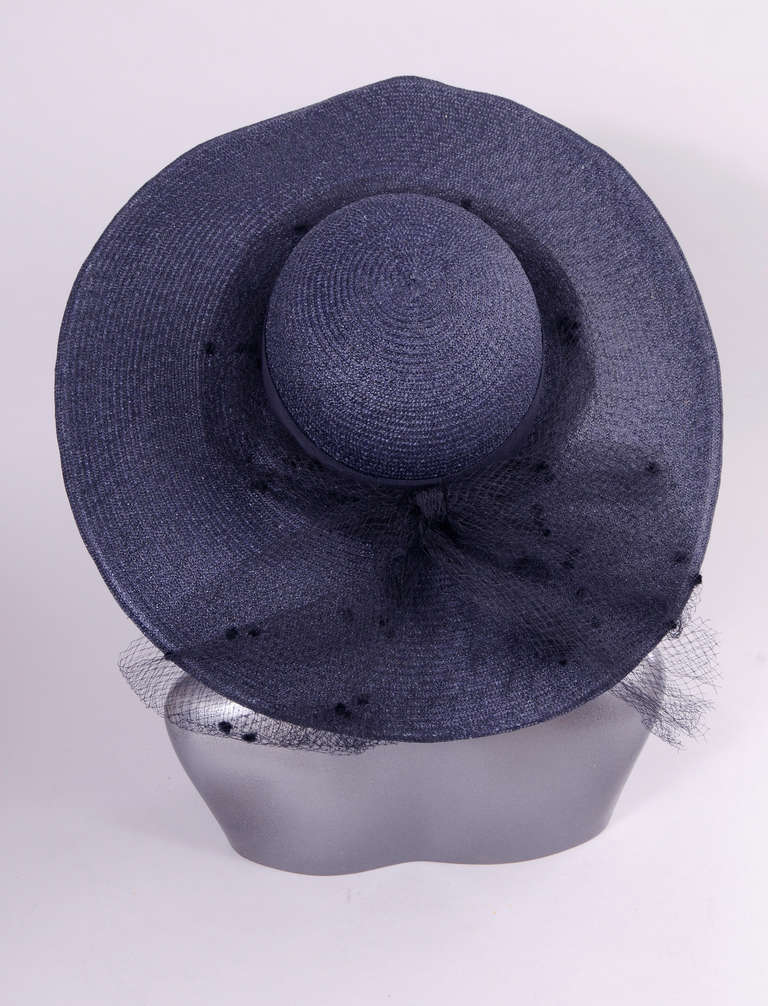 """A broad brimmed navy blue straw hat from the 1950's is trimmed with a matching navy point d'esprit tulle hat band and bow. It is in excellent condition. Measurements; Height 5"""" Diameter 19"""" Interior circumference 22"""""""