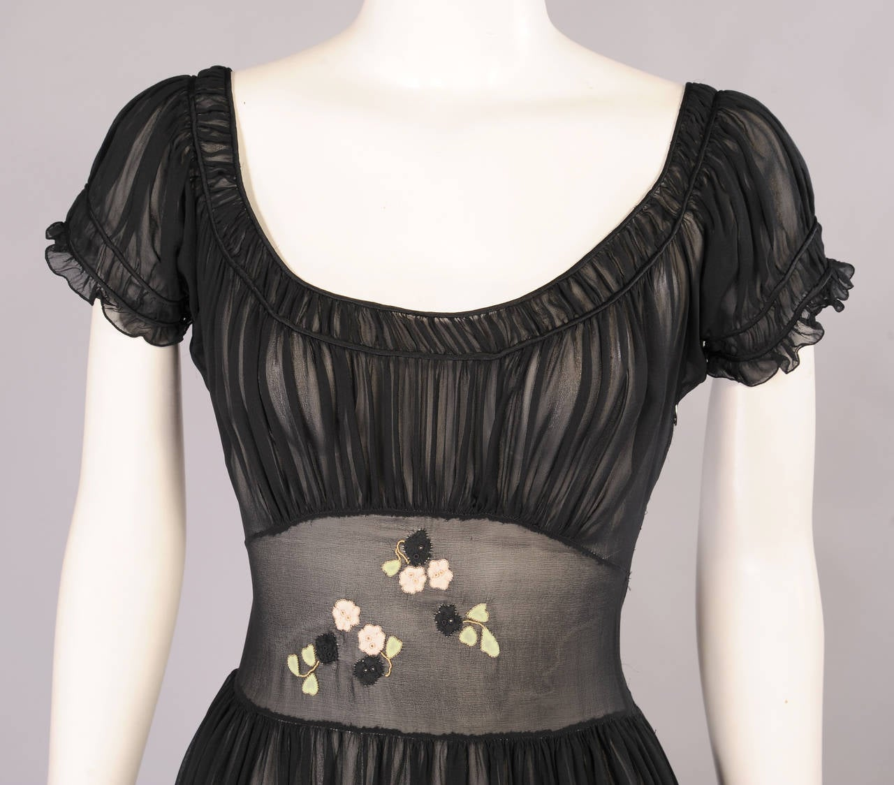 Sheer black silk chiffon is appliqued with pink and black flowers and green leaves. The bodice is gathered at the scoop neckline over a wide flat waistband. The skirt is gently gathered and there is a left side zipper. The dress appears to be