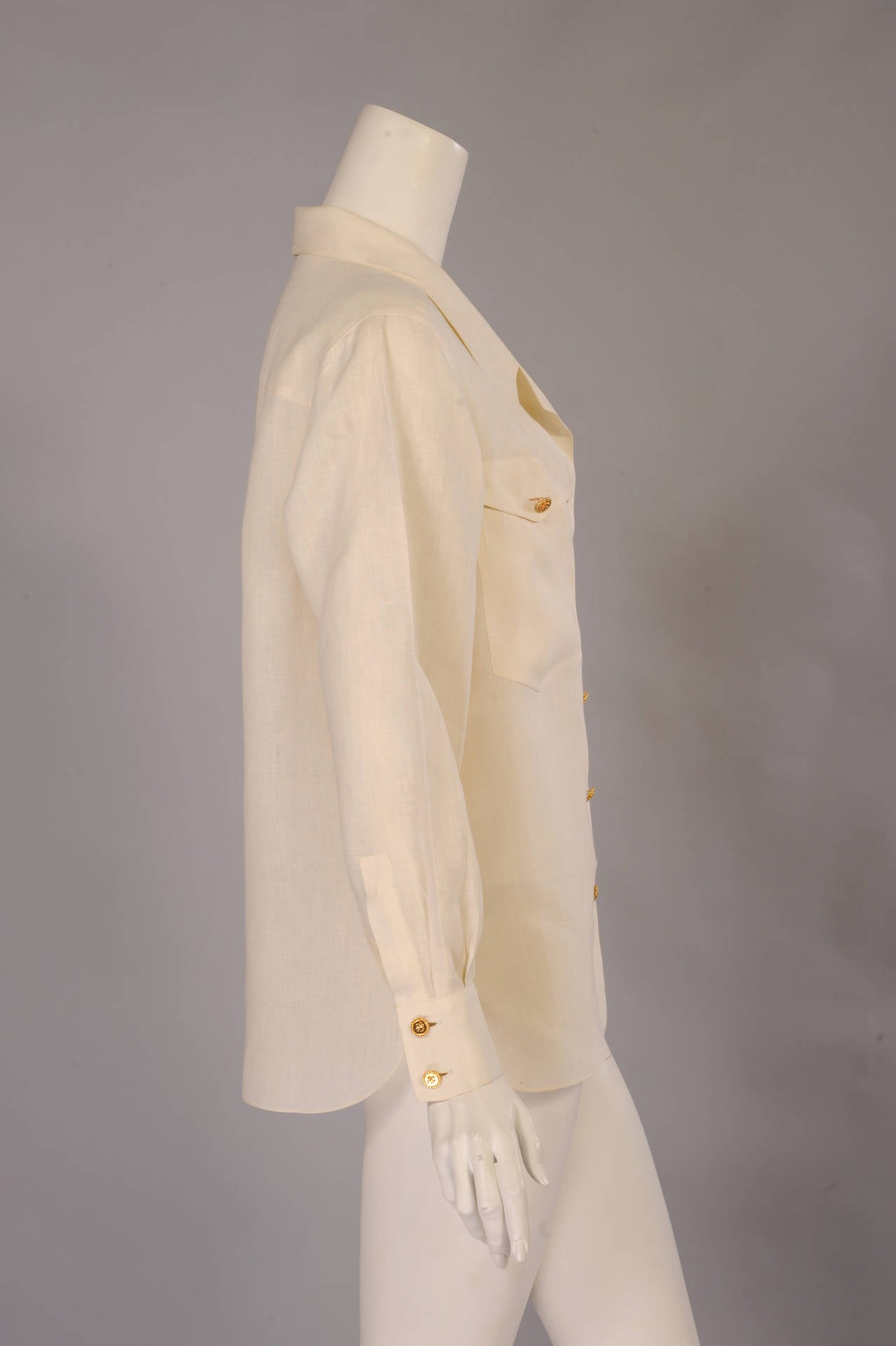 A classic blouse in cream linen from Chanel has two breast pockets and Chanel buttons. The extra button is sewn inside, and the blouse appears unworn.
