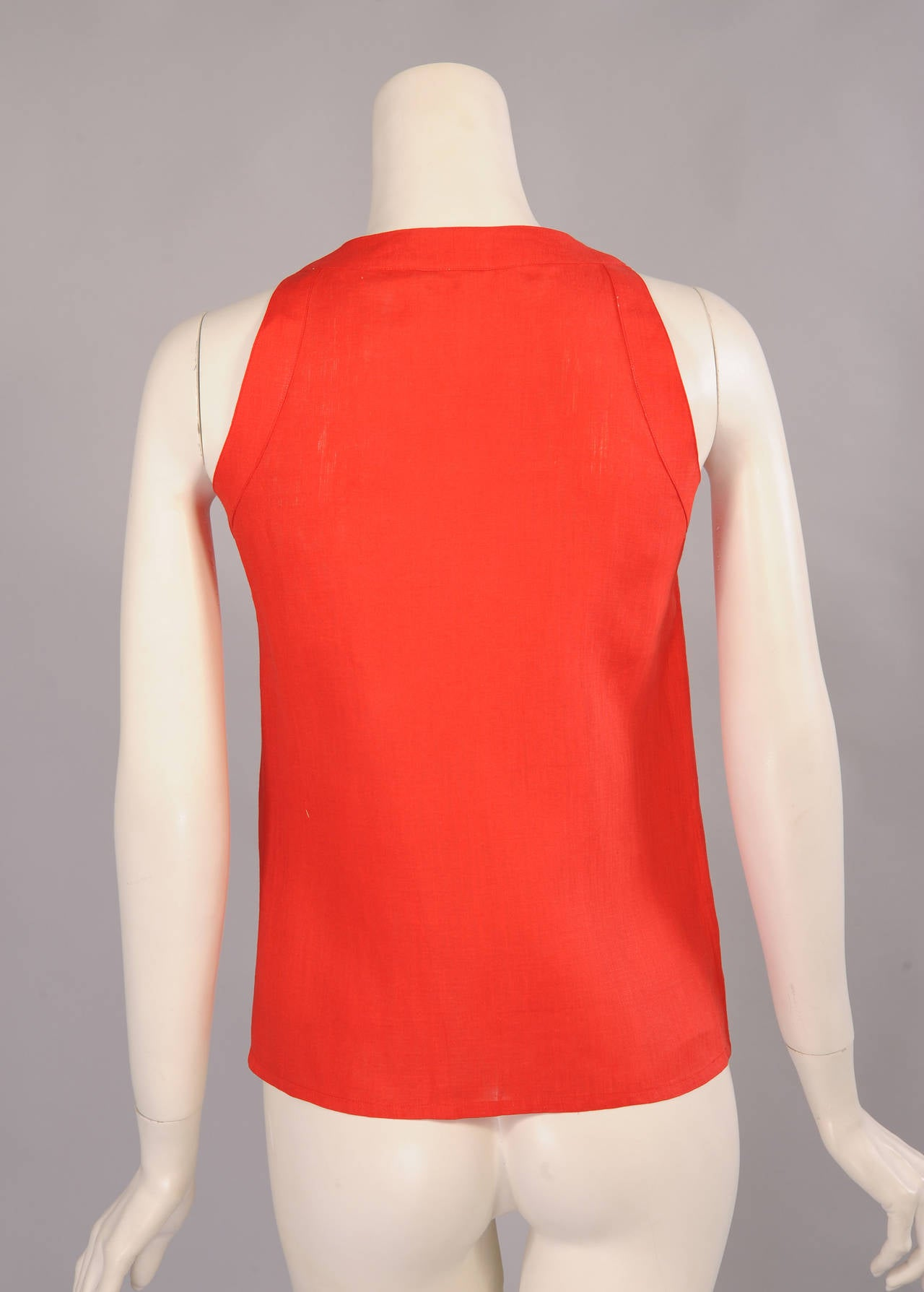 Bright red linen is pleated on either side of the covered button front of the sleeveless and collarless blouse from Chanel. It is in excellent condition.
