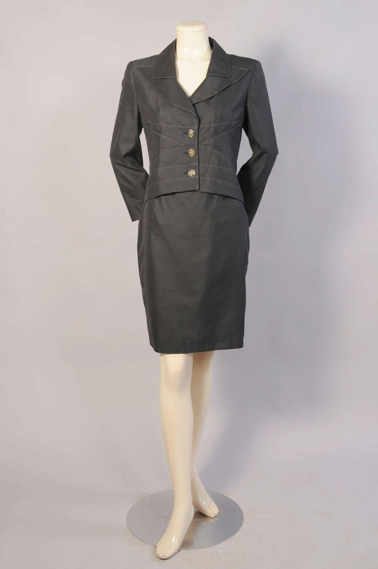 A blend of silk and cotton, this suit has a cropped jacket with decorative stitching and a three button closure. The straight skirt has a center back zipper. Both pieces are fully lined and in excellent condition. Measurements; Jacket  Shoulders