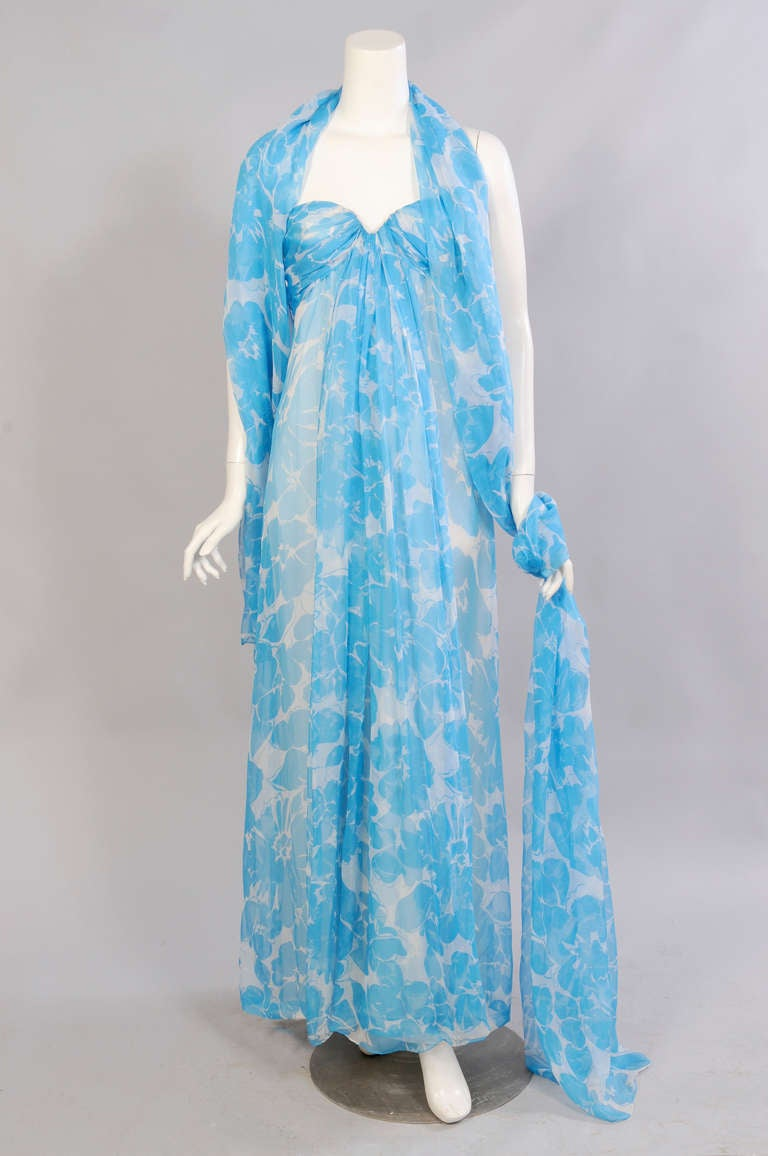 Lush tropical flowers in a beautiful and brilliant shade of blue on sheer white silk chiffon create a stunning summer evening dress and wrap. The strapless gown has a boned interior corset with a petersham and interior zipper. The chiffon drapes and