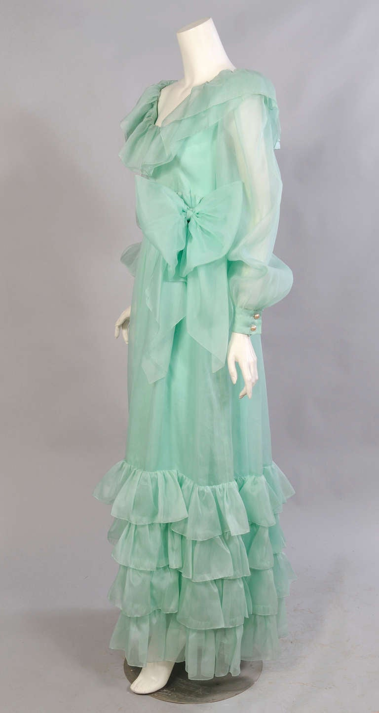 Ultra feminine, this aqua silk organza dress from Givenchy Haute Couture has a ruffled neckline and hemline as well as a large bow at the waist. The dress has a center back zipper and pearl buttons on the cuffs. It has all the hand finishing that