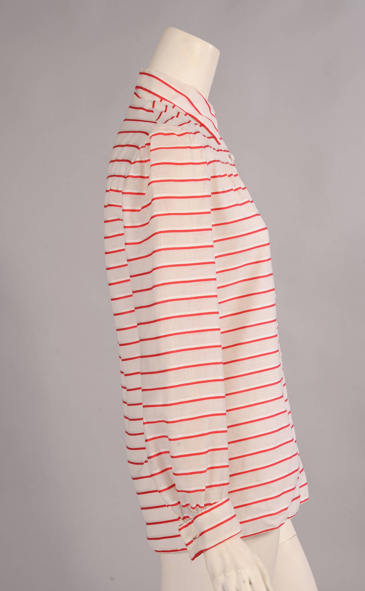 Red and white shadow striped cotton is used for this classic blouse with front and back yokes from Chanel Haute Couture. The blouse has white fabric covered buttons and cuffs that require cuff links. The body of the blouse is lined in white cotton
