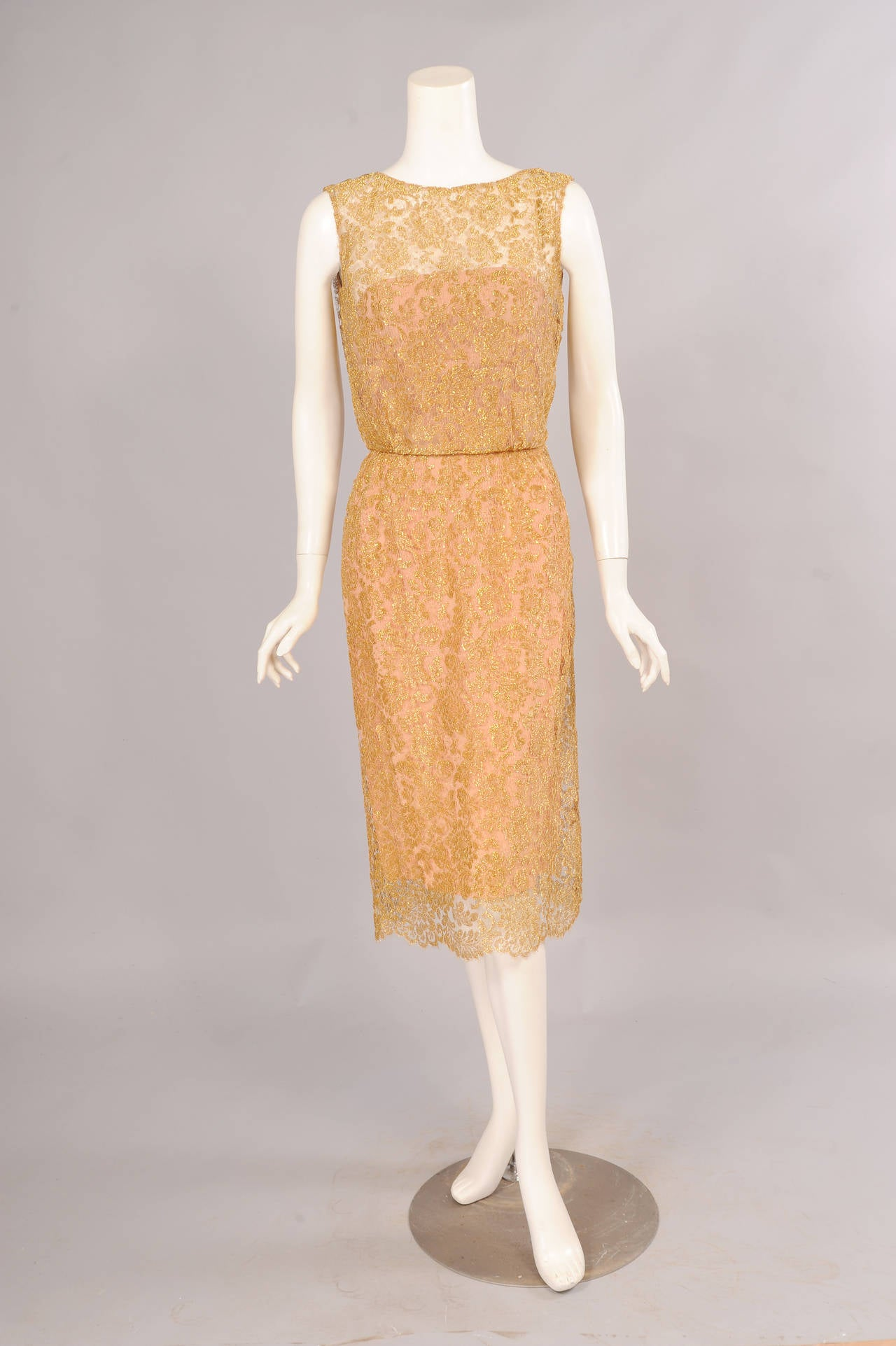 Beautiful gold lace is lined with a rose pink silk strapless sheath creating the look of a rose gold evening dress. The dress opens on the left shoulder and side with hooks and eyes, snaps and a zipper. It is in excellent