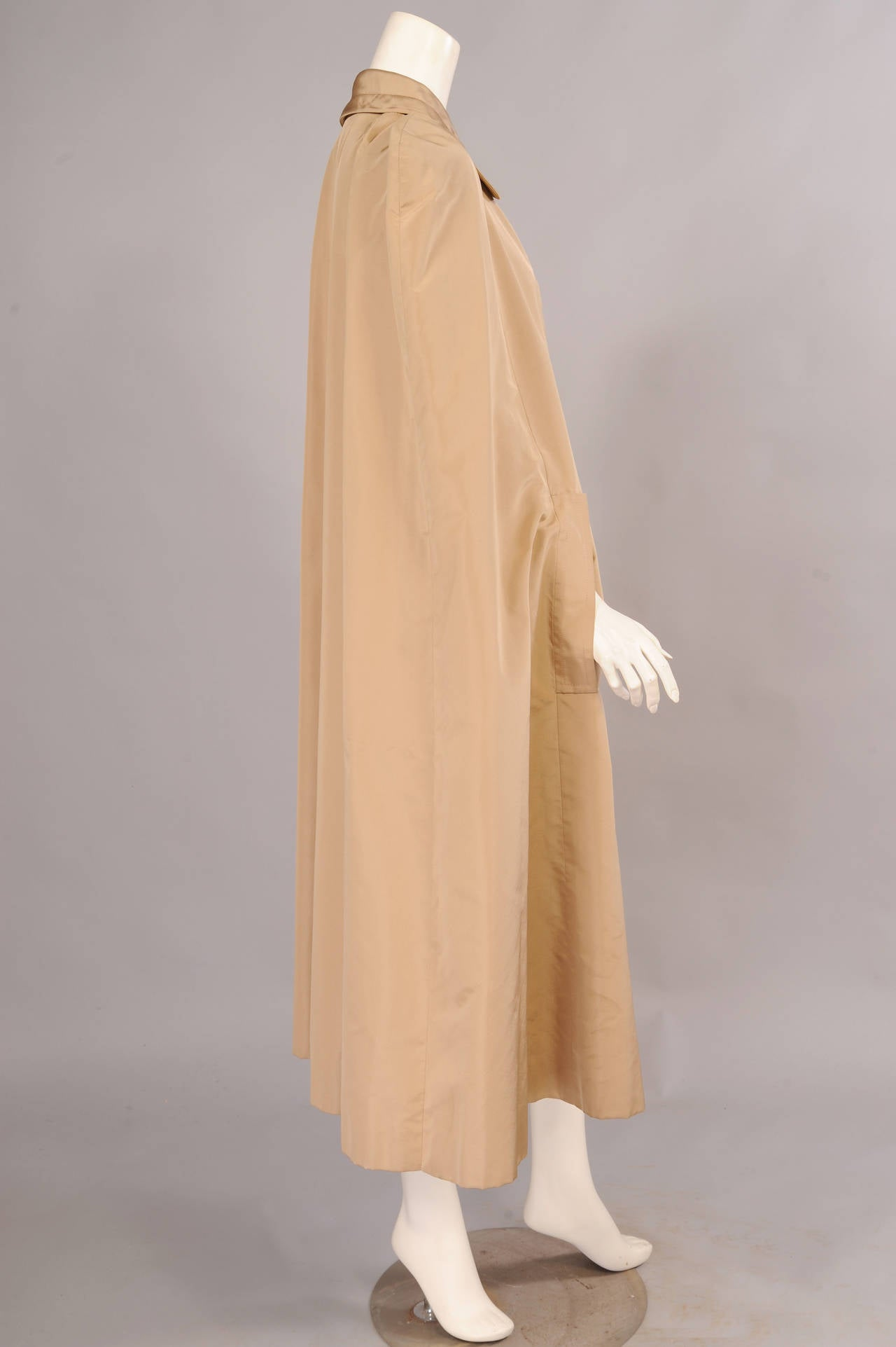 Classic and elegant, this silk faille cape has a hook and eye closure and two openings for your arms. It is fully lined in matching silk and bears the couture label as well as remnants of the runway label. It is in excellent condition. One size fits