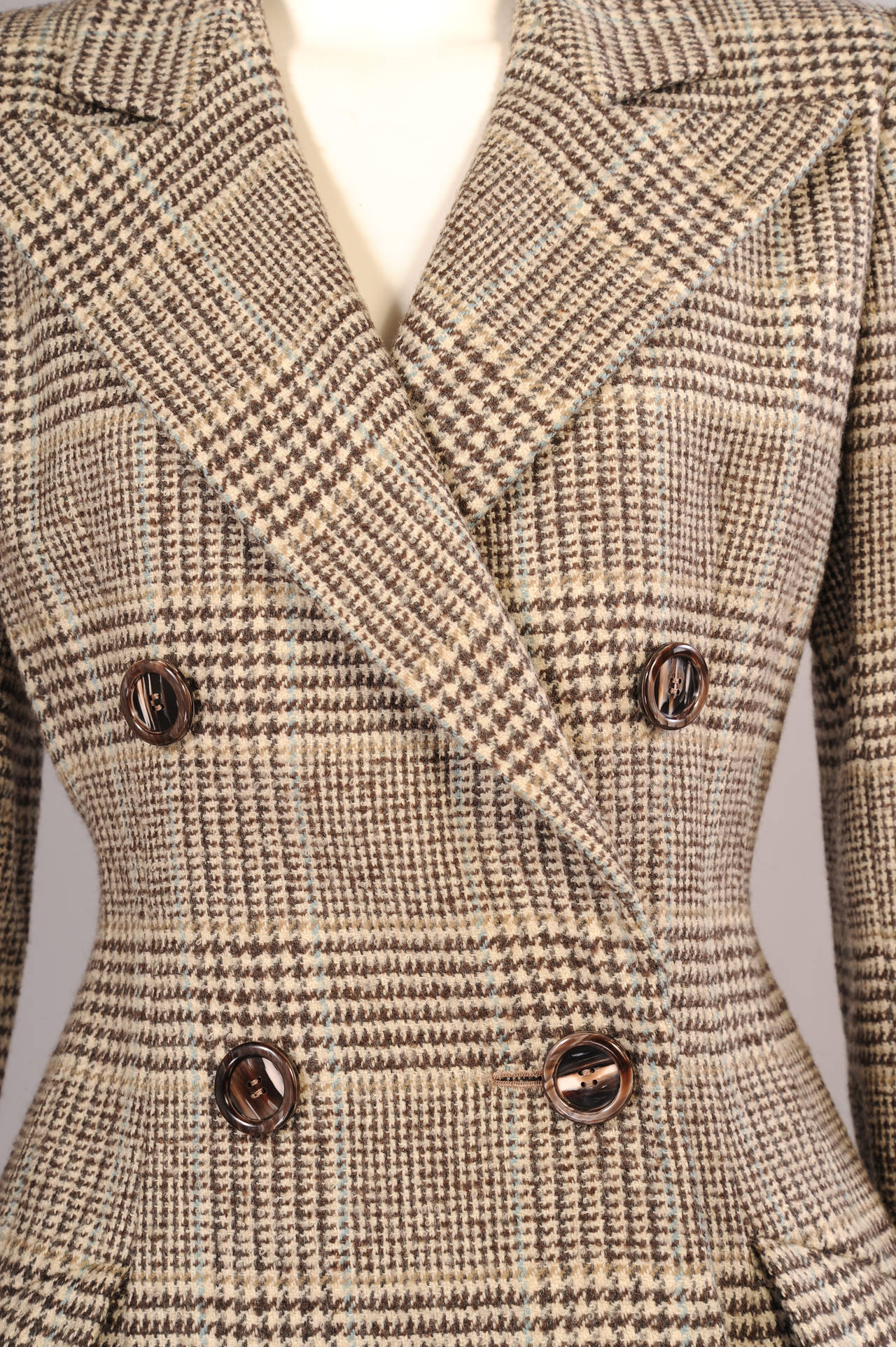 Christian Lacroix has taken a classic menswear look and added a feminine twist with his expert tailoring. Made from a brown and cream wool, the plaid has a faint blue stripe running through it. The jacket is fully lined and it is in excellent