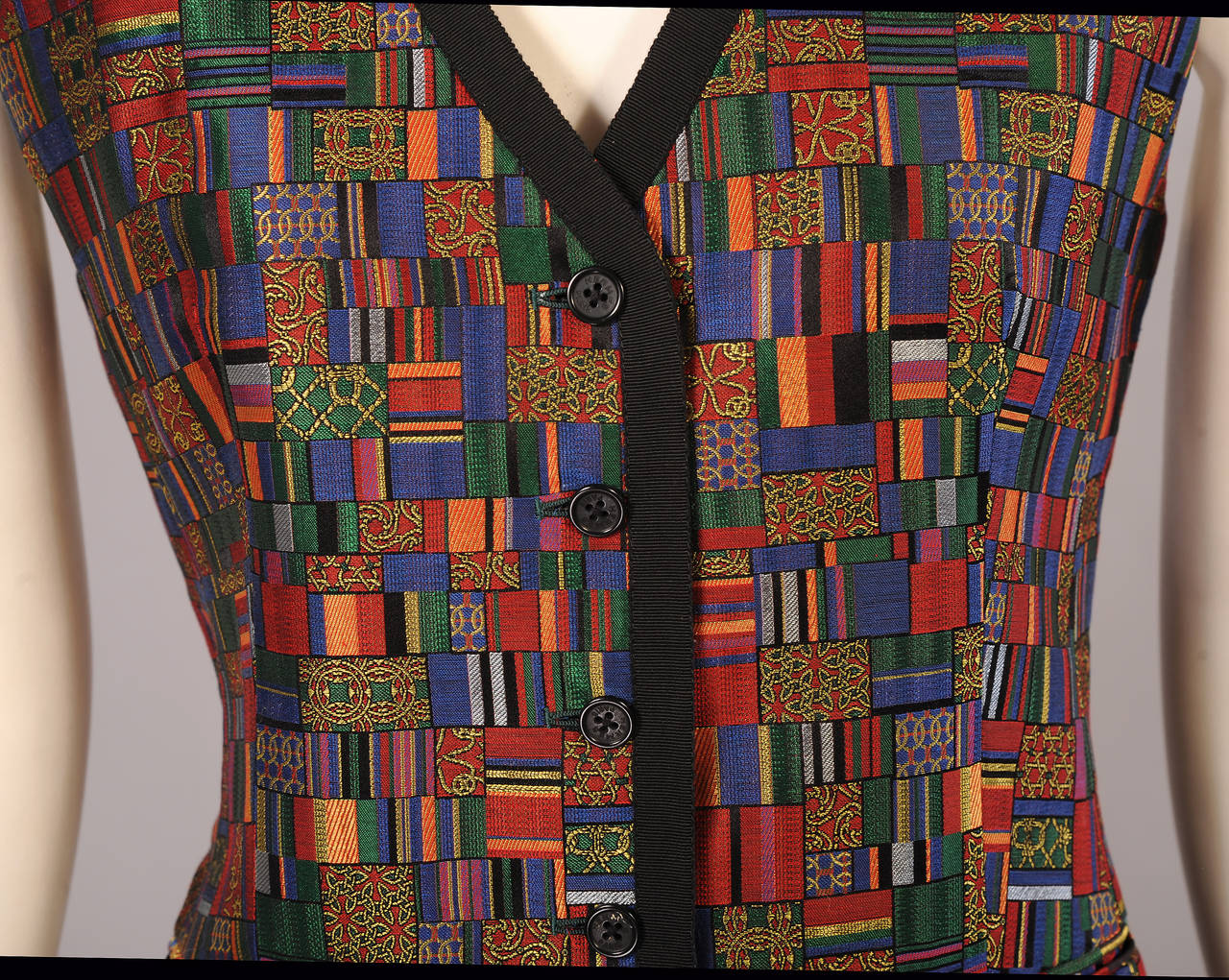 Rich jewel tones are accented with black trim at the neckline and center front of this vest. There are two pockets which are still sewn shut. The back of the vest is black silk in a woven Hermes logo ribbon pattern. This is also used for the lining.
