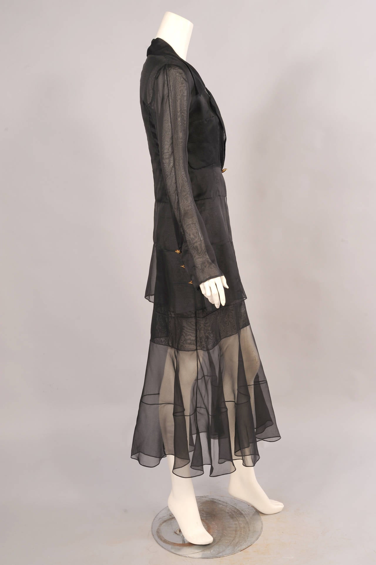 Inspired by the 1920's designs of Coco Chanel this sexy sheer black silk dress in single and double layers of silk creates a very eye catching dress and jacket ensemble. The dress is sewn in vertical panels at the top and double horizontal panels on