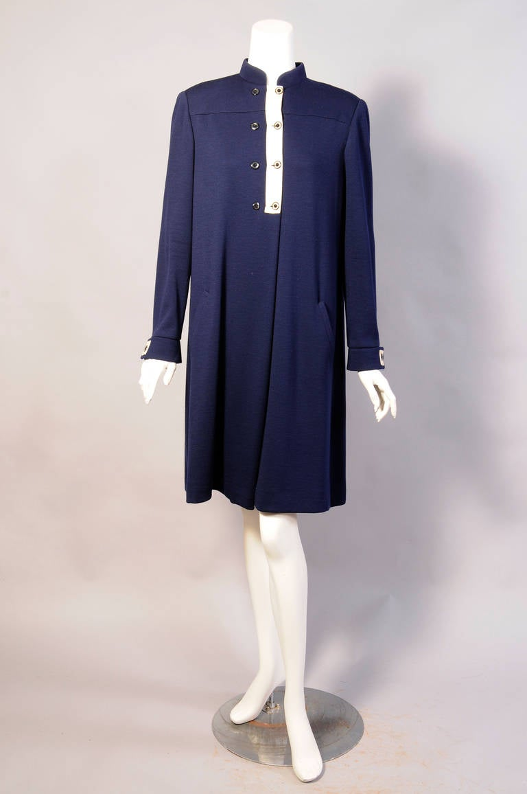 Spare and elegant this navy blue wool dress slips on over your head. The button front and cuffs are trimmed with cream colored canvas with navy rimmed clear buttons. The dress has two pockets and it is in excellent condition. Measurements Shoulders