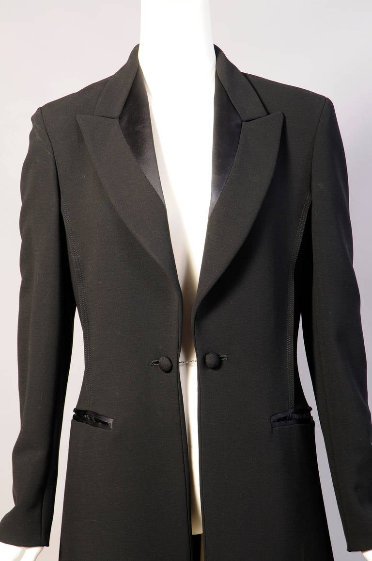A classic tuxedo jacket or tail coat is the inspiration for this elegant long coat made from fine black wool with black satin lapels and cuffs. The coat has two large buttons on a chain at the center front and cufflinks on the satin French cuffs.