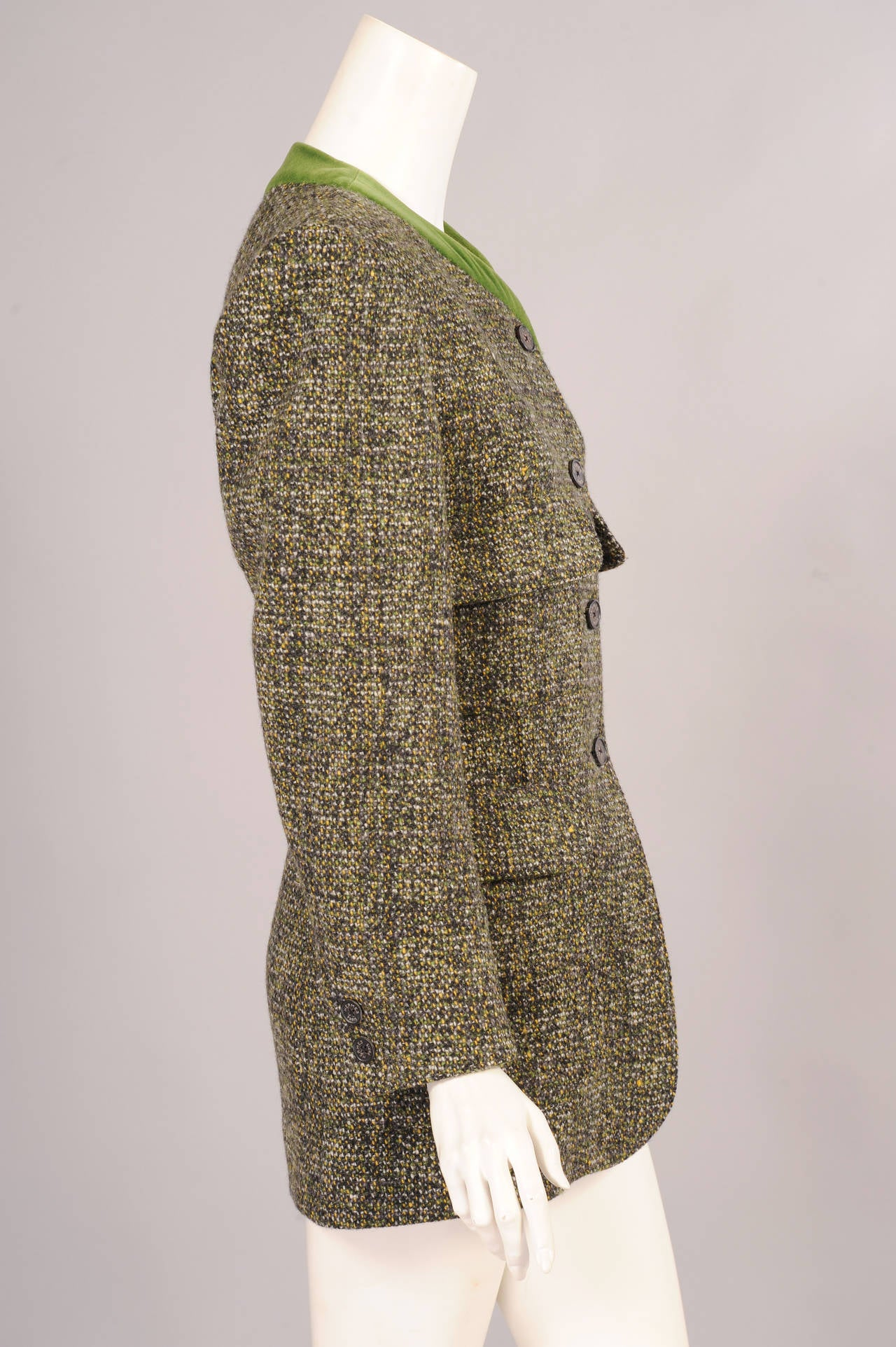 The moss green velvet collar of this jacket compliments the green wool tweed beautifully. The jacket has four generous pockets, Hermes stamped buttons at the center front and on the sleeves, and a wonderful red silk lining which is woven with the