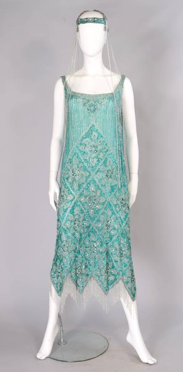 A beautiful shade of blue green silk is completely covered in beads. There are bugle beads, caviar beads and hundreds of sparkling rhinestones all set against rows and rows of opalescent green sequins. The dress has deep slits on each side and the