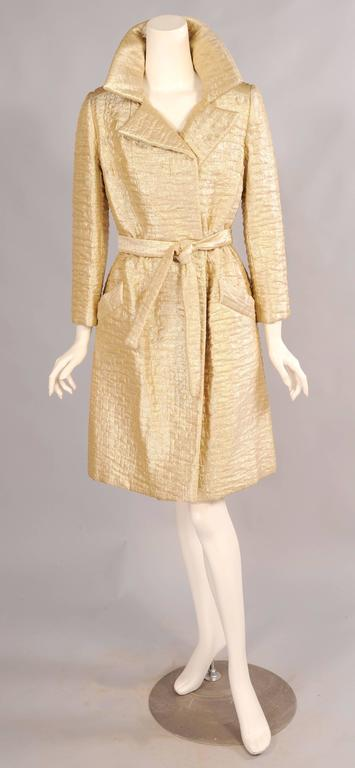 Timeless styling makes this great gold lame trench coat a perfect fit for any wardrobe. Retailed by Bonwit Teller in the 1960's the coat simply ties closed with a matching belt to accommodate a range of sizes. It is fully lined and in excellent