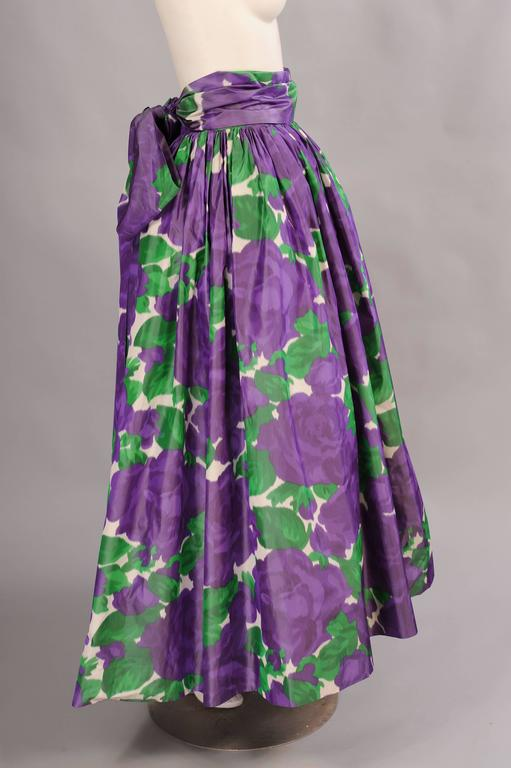 The sound of silk taffeta is synonymous with elegant evening dresses. This stunning evening skirt of large scale lavender cabbage roses and green foliage is given extra volume by the deep emerald green ruffled petticoat peeking out from the hemline.
