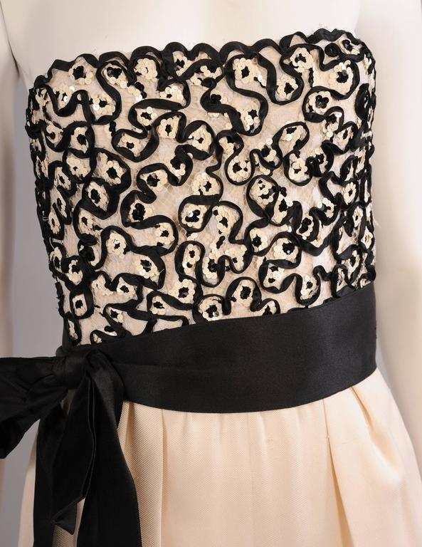 A cream lace bodice is embellished with narrow black satin ribbon and white sequins. The pants are all silk. The black cummerbund is not original to the piece but it looks great. The original belt is cream silk with a cream buckle.  The backing is