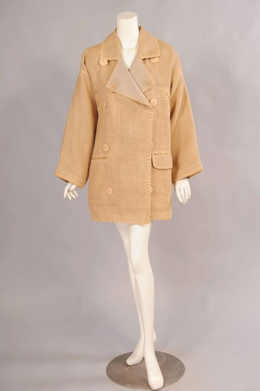 A loosely woven linen is edged with raffia and fastened with bamboo buttons for a very natural, eco friendly garment. The jacket is cut full, it is double breasted with two sets of buttons so it can be worn by a man or woman. There are two diagonal