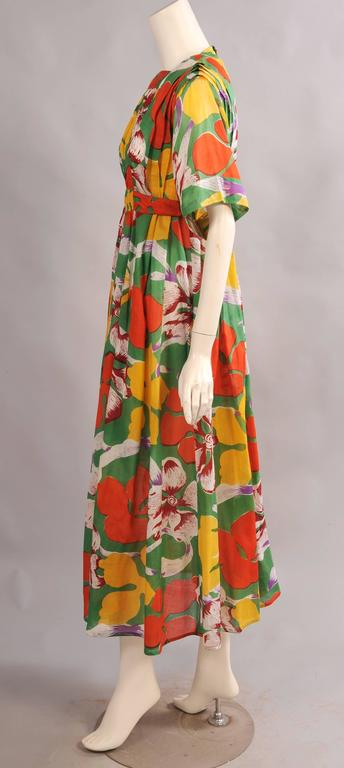 Colorful large scale tropical flowers on a bright green cotton background make this a great summer dress designed by Jean Muir in the 1970's. The dress has a square neckline, vertical pleats on the bodice, two [pockets and an attached belt. It