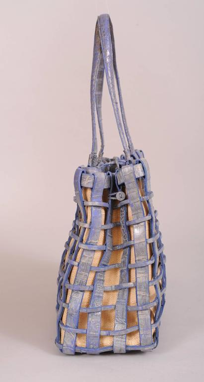 A woven blue crocodile cage bag matches the blue crocodile top edge of the removable woven raffia straw bag insert. This bag is lined in pale blue suede. it has a center zipped compartment and two open sections. One of these has a zippered pocket