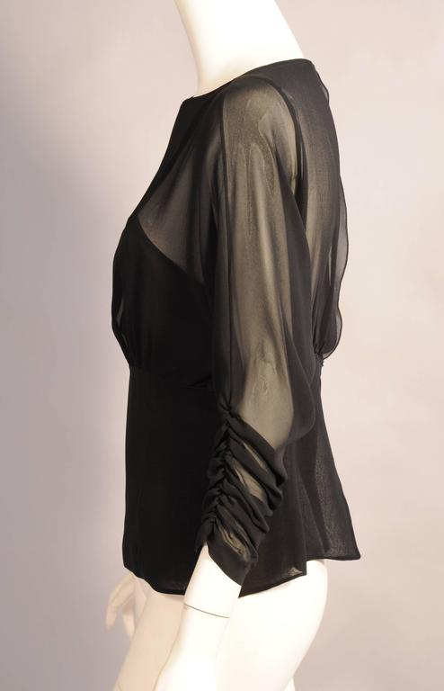 Black silk chiffon is used for this blouse and the attached camisole designed by Karl Lagerfeld. The blouse has a scoop neckline, empire waist and beautifully gathered sleeves. It closes with a button and loop at the neckline and the waist. It is in