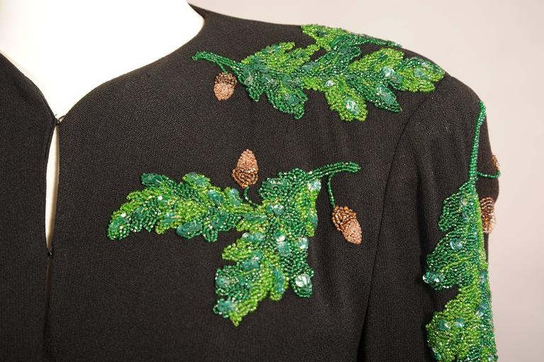 This clean lined 1940's black crepe jacket has a five button closure, two faux pockets and fantastic beaded decoration.  The oak leaves are done with caviar beads in several shades of green which are enhanced with green sequins for added depth of