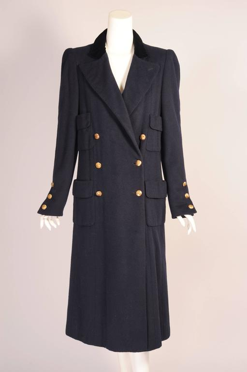 A timeless navy blue double breasted coat from Chanel has logo buttons, four patch pockets, a velvet collar and a warm and toasty mink lining. This coat is in excellent condition and just in time for the chilly days ahead. Measurements; Shoulders