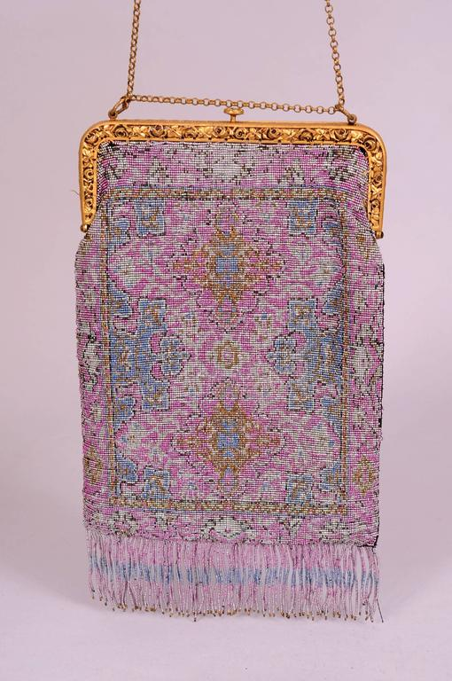 This stunning evening bag from the teens is worked in an unusual color combination using cut steel beads. Lavender, blue, silver and gold are the predominant colors in a design that is reminiscent of an Oriental carpet. The bag has a gold toned