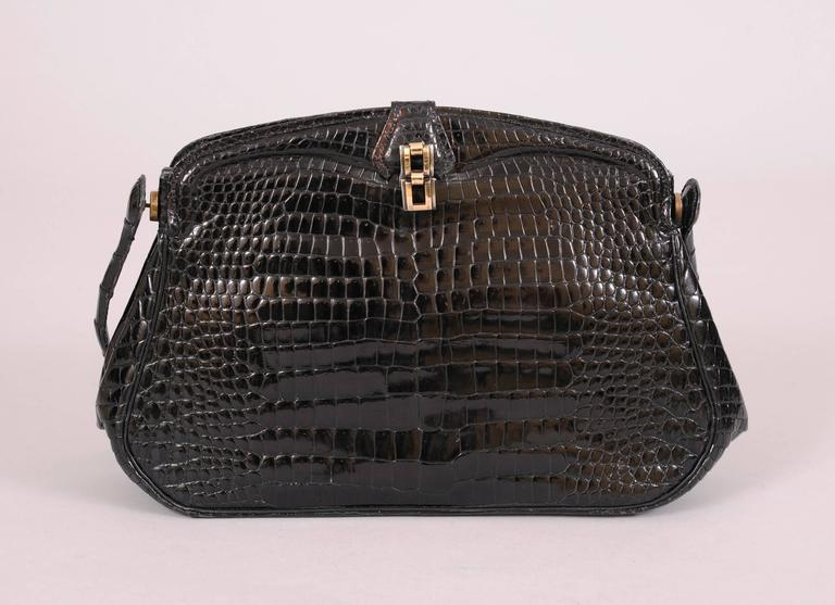 This elegant black crocodile evening bag is made from beautiful matched skins on the front and back. The handle swings down to create a clutch. There is a hallmarked sterling silver and gold clasp. The leather lined bag has two open sections and a