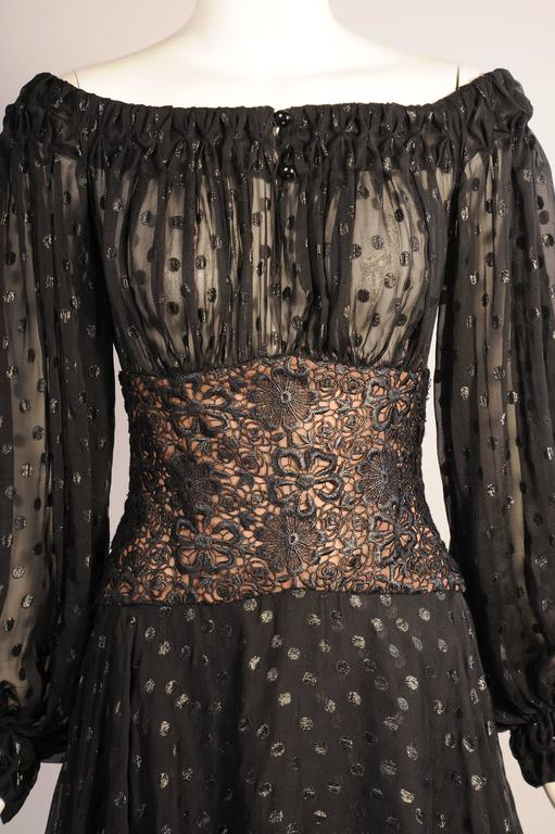 Sheer black silk chiffon is woven with glistening black polka dots for this figure flattering evening gown. The sheer bodice has a gathered neckline, two buttons at the center front, and long full sleeves with two button cuffs. The fitted black lace