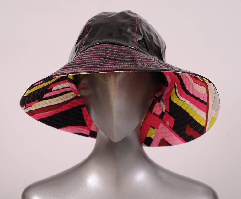This hat will brighten the worst rainy day. A shiny black exterior is stitched with hot pink thread on the crown sections as well as the channel quilted brim. The interior is a burst of beautiful colors in a Pucci cotton print. Every shade of pink
