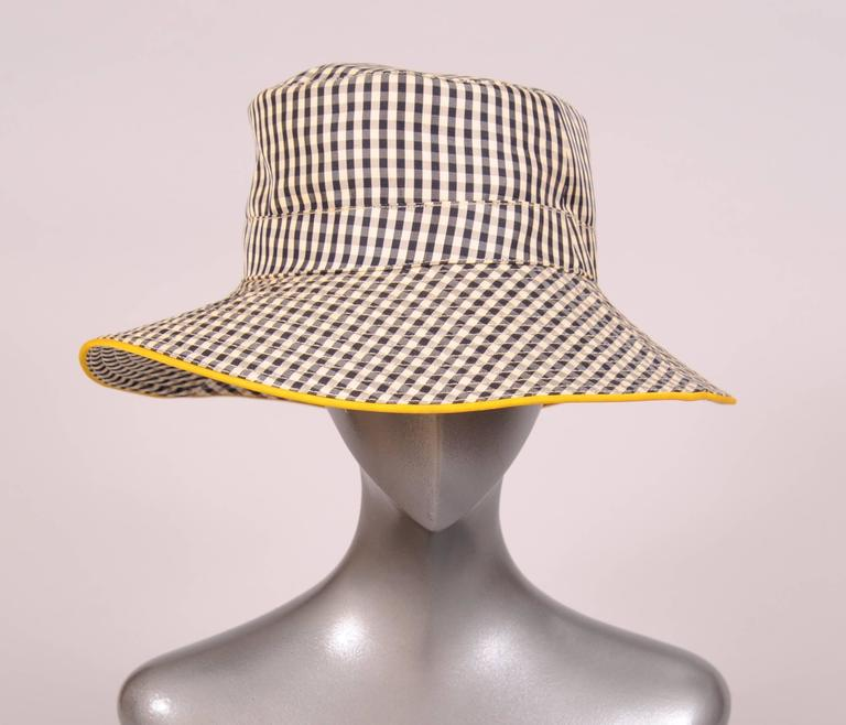 This charming black and white checked silk hat has a brim edged with daffodil yellow silk. The brim is channel quilted and the hat band has an embroidered H on the right side. This great hat is in excellent condition and marked a size