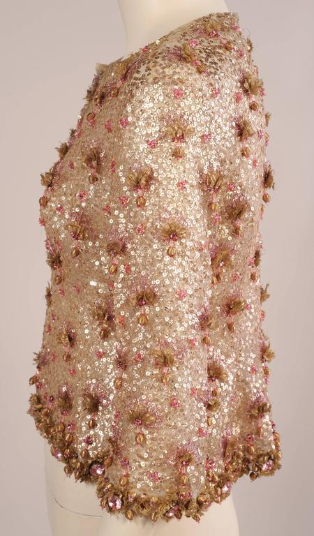 This stunning tulle evening jacket is covered with tiny gold sequins, gold lame flowers, pink tinsel embroidery, pink prong set rhinestones and gold wrapped dangling beads. The sleeves and the hem are heavily beaded with very large pink prong set