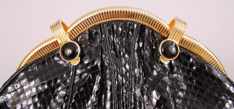 A curved gold toned frame with two onyx clasps sets this black snakeskin Judith Leiber bag apart from others. The added height allows room for larger cell phones. The bag has an optional snakeskin shoulder strap. It has an interior logo plaque and