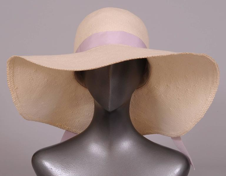 "A feminine white straw hat is trimmed with a lavender ribbon and a bouquet of violets, perfect for a sunny summer day. It is in excellent condition. Two of these hats are available. Measurements; Height of crown 5 1/2"" Width 17"