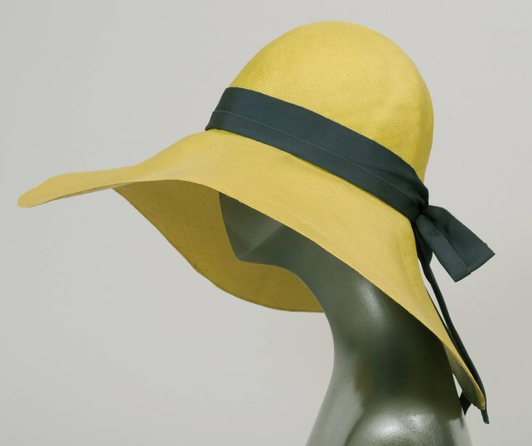 A broad floppy brim adds glamour and mystery to the wearer of this finely woven chartreuse straw hat designed by Adolfo. The crown is trimmed with a navy blue gros grain ribbon hat band. This hat is in excellent condition. Measurements; Interior