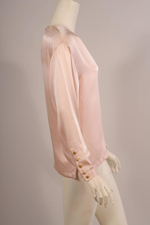This gorgeous pale pink silk charmeuse blouse just slides on over your head. There is a shamrock button and silk loop at the center back. The long sleeves have five matching buttons with shamrocks. The hemline is split on each side so that the