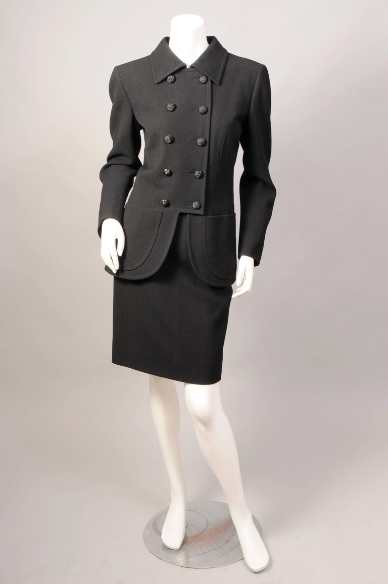 This late 1970's or very early 1980's black wool suit from Yves Saint Laurent  Haute Couture is a stunning example of true French couture tailoring. Made in the YSL atelier in Paris the suit has a great deal of hand finishing in the couture manner.