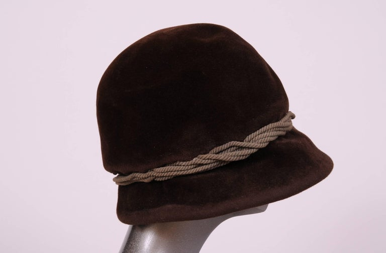 A rich chocolate brown velour is accented by a grey/green woven band on this hat from Balenciaga Haute Couture. The crown of the hat is soft and can be shaped in a variety of ways. The brim is wider in the front and has a rigid form. There is an