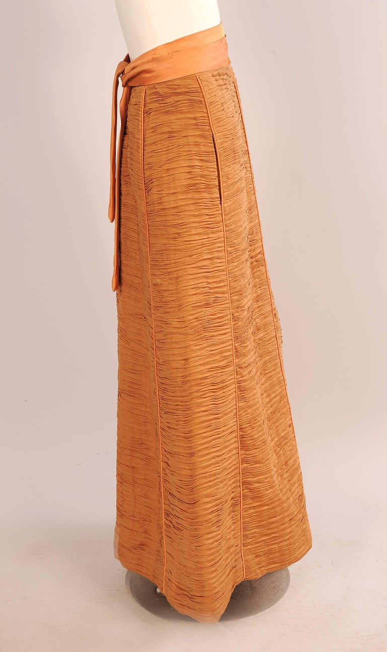 Sybil Connolly is most famous for her extremely rare pleated linen clothing. Each garment used nine yards of linen to make one yard of pleated linen. This stunning melon colored linen skirt is lined in matching silk. It is all hand finished in the