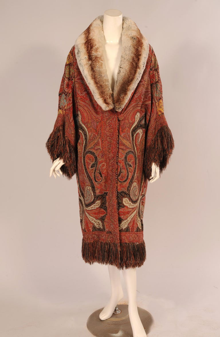 A beautiful antique handmade wool Kashmiri paisley shawl, made in India has been used to make this dramatic 1920's Coat with a chinchilla collar and multi-color silk fringe trim. The pattern has been laid out to great advantage, making the best use