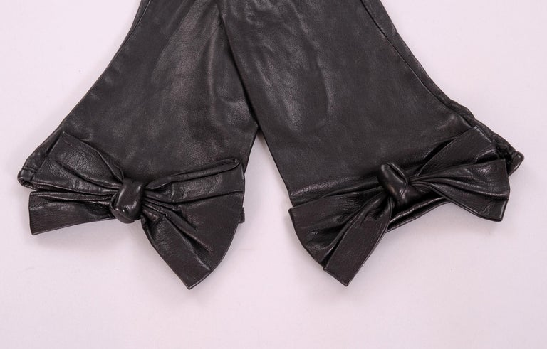 These butter soft black leather gloves designed by Carlos Falchi have a wonderful leather bow and knot at the wrist. They are lined in black silk and marked a size 7. Never worn, they are in pristine condition.