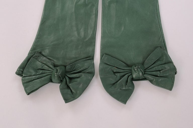 These butter soft deep green leather gloves designed by Carlos Falchi have a wonderful leather bow and knot at the wrist. They are lined in black silk and marked a size 7. Never worn, they are in pristine condition.