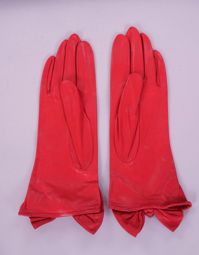 These butter soft red leather gloves designed by Carlos Falchi have a wonderful leather bow and knot at the wrist. They are lined in red silk and marked a size 7 1/2.. Never worn, they are in pristine condition.