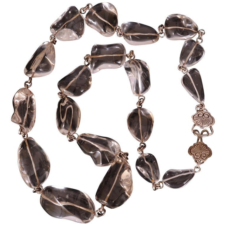 Smooth and cool to the touch this long polished rock crystal necklace goes with everything in your wardrobe. The stones are various shapes and sizes with silver links and clasp. It is signed Stephen Dweck and is in excellent