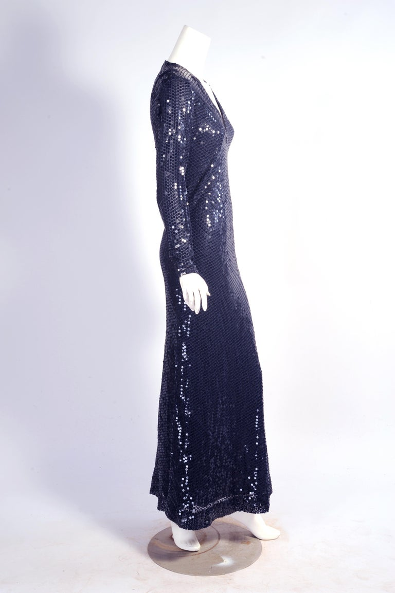 A classic 1970's shape, V shaped neckline, long sleeves, and a body skimming silhouette are key elements of this dress from Bill Blass. It is a sheer navy silk lined in navy silk. The dress has a center back zipper and it is in excellent condition.
