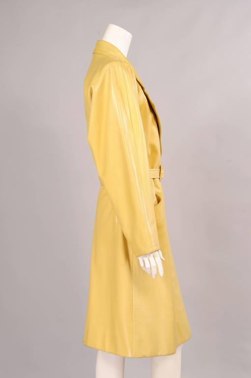 Supple leather in a beautiful shade of soft yellow is unexpected and striking in this leather trench coat from the Givenchy Couture runway. Notched lapels, a matching yellow leather belt and two hip pockets add to the classic look. The coat has a